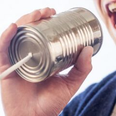 Man talking into a can with a string
