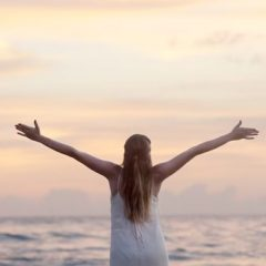 Triumphant woman facing ocean with arms stretched out with excitement